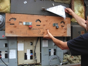 Jurgen shows me the plywood barricade he had  placed over his three remianing analogue meters, with holes cut for meter-reading. BC Hydro broke the locks off the plywood to force a smart meter on him. (Photo © Kim Goldberg)